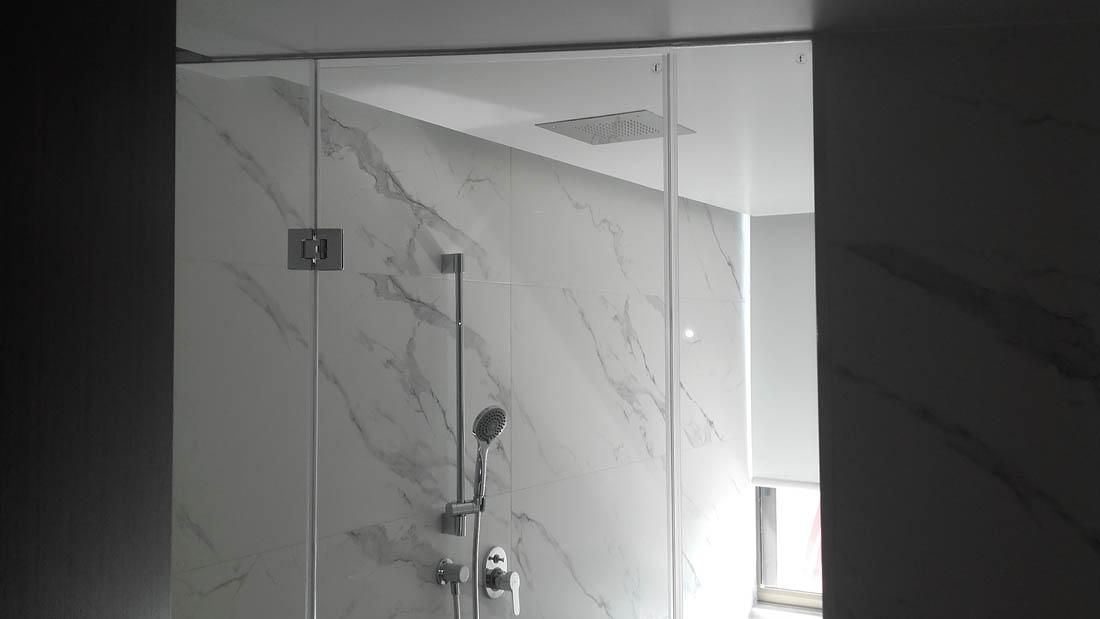 Ανοιγόμενη πόρτα ντουζιέρας σε εσωτερικό μπάνιου με πλακάκι από μάρμαρο