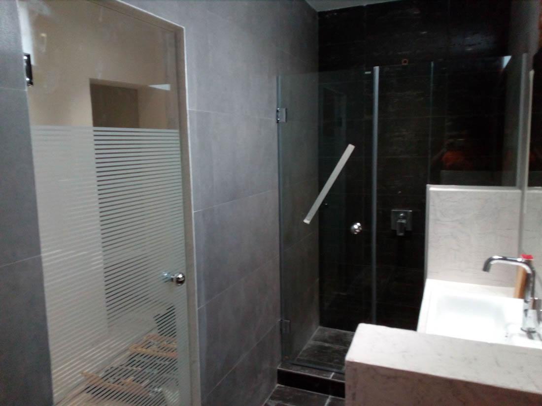 Ανοιγόμενη ντουζιέρα σε εσωτερικό μπάνιου υπό κατασκευής. Γυάλινη ανοιγόμενη πόρτα μπάνιου με ριγέ άσπρο