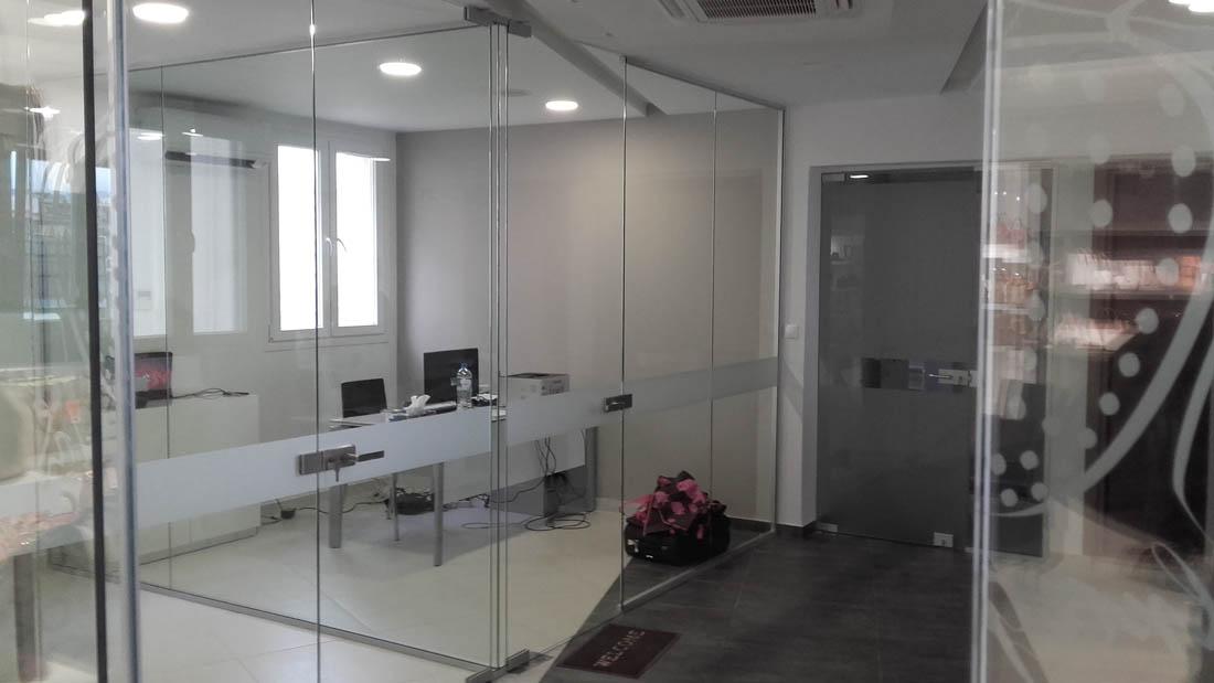 Γυάλινες ανοιγόμενες πόρτες σε εσωτερικό εταιρείας που διαχωρίζει το κάθε γραφείο