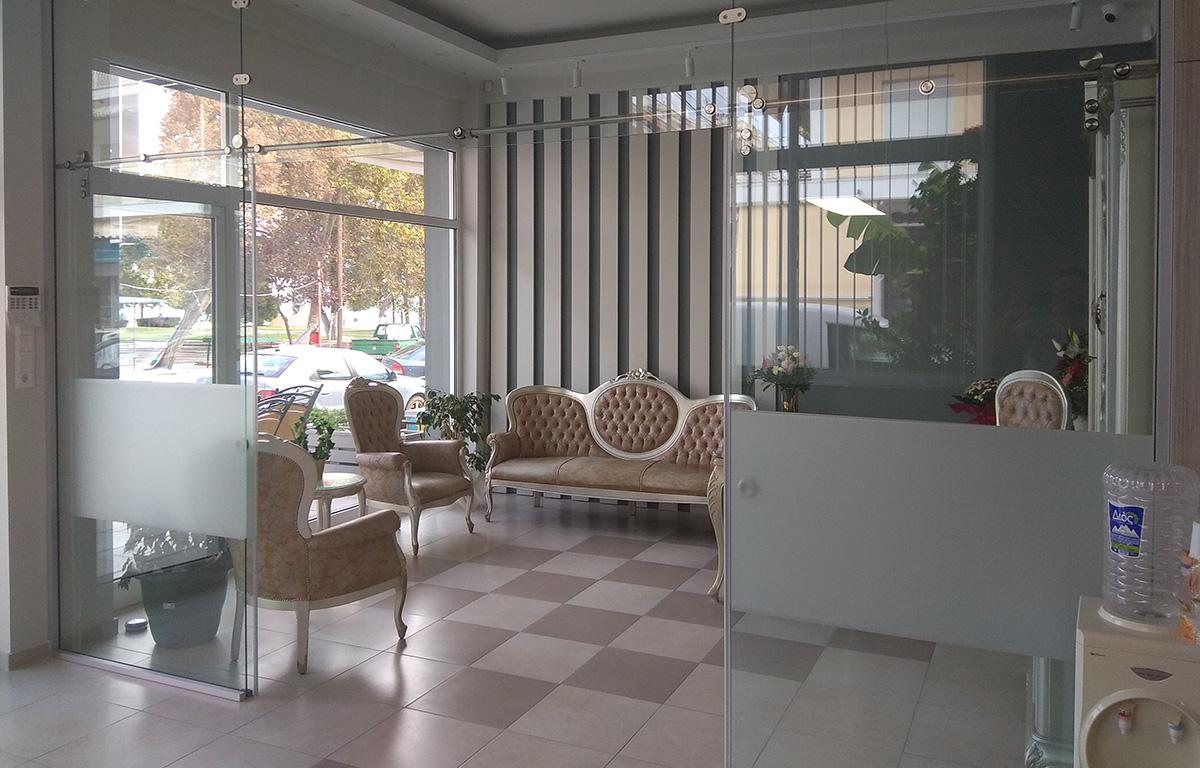 Γυάλινες Συρόμενες πόρτες σε χώρο υποδοχής καταστήματος, με ωραία σαλόνι