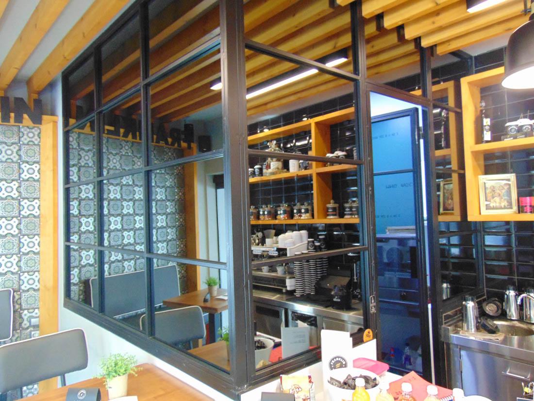 Καθρέφτης και γυάλινο διαχωριστικό σε κουζίνα μαγαζιού εστίαστης.