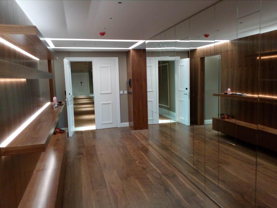 Ντουλάπα - καθρέφτης σε εσωτερικό ξύλινου δωματίου. Υπάρχουν ράφια με κρυφό φωτισμό.
